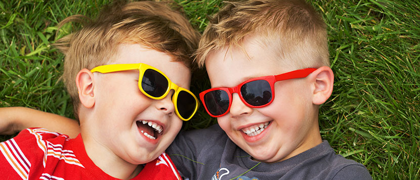young boys wearing sunglasses laughing outside